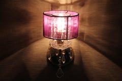 Den rosa lampan gjuter en skugga på väggen Arkivfoto