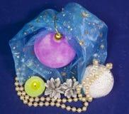 Den rosa sammetslena bollen för ` s för det nya året, den brinnande stearinljuset och en pärla pryder med pärlor på en blå bakgru Royaltyfri Foto