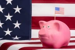 Den rosa sparbössan för pengar är värd på bakgrund amerikanska flaggan Royaltyfria Bilder