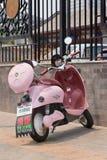 Den rosa sparkcykeln parkerade framme av ett staket, Peking, Kina Arkivfoton