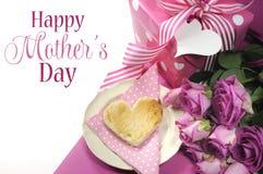 Den rosa temafrukosten med hjärta format rostat bröd, rosor och prickgåvan med lycklig moderdag tar prov text Arkivfoto