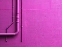 Den rosa väggen med leda i rör Arkivbild