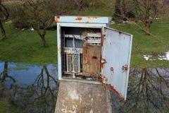 Den rostade elektriska föreningspunktasken för metall med den öppna dörren monterade på konkret pol royaltyfri bild