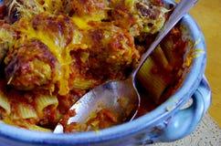 Den rostfria skeden i en keramisk eldfast form fyllde med bakade pasta och köttbullar Royaltyfria Bilder