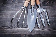 Den rostfria skyffeln krattar murslevgaffeln på att arbeta i trädgården för träbräde som är conc Royaltyfri Bild