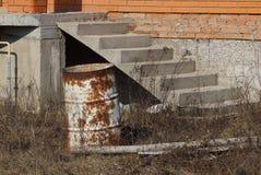 Den rostiga gamla trumman står i torrt gräs nära huset med en stege fotografering för bildbyråer