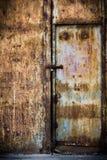 Den rostiga gammala bruntet belägger med metall dörren Arkivfoton