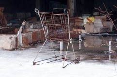 Den rostiga korgen och brutet möblemang, i förstört, shoppar i Pripyt, Tjernobyl arkivfoto