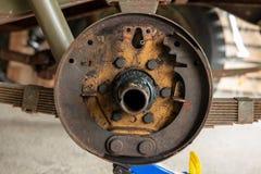 Den rostiga valsbromsen, en jeep för valsbroms demontera i ett garage royaltyfria foton