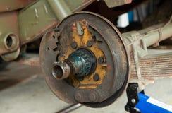 Den rostiga valsbromsen, en jeep f?r valsbroms demontera i ett garage arkivbild