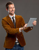 Den röra unga affärsmannen en tablet avskärmer. Arkivfoto