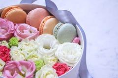Den runda asken med blommor och mandelkakor marmorerar p? bakgrund royaltyfri fotografi