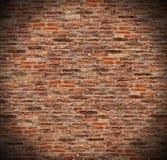 Den runda cirkelstrålkastaren på väggen för röd tegelsten, radiell lutningskugga på gammal mörk brunt, orange tegelsten fäktar Royaltyfri Foto