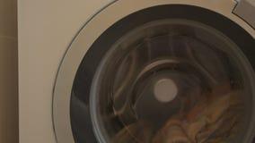 Den runda dörren av den vita tvagningmaskinen arbetar och vänder med kulör kläder Tvagningmaskinen är tvättade handdukar stock video