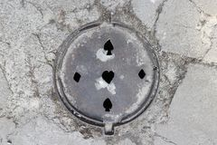 Den runda metallluckan med hål i form av kort passar i stads- trottoar royaltyfri foto