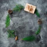 Den runda ramen av julgåvaasken, vinterträdfilialen och sörjer kottar på mörk bakgrund nytt år för sammansättning Lekmanna- lägen royaltyfria bilder