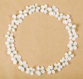 Den runda ramkransen som göras av den vita våren, blommar på bakgrund för brunt papper Lekmanna- lägenhet Royaltyfri Bild