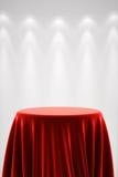 Den runda sockeln med rött silke och fläcken tänder Arkivfoto