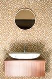 Den runda spegeln med den keramiska vasken och silver knackar lätt på Royaltyfria Foton