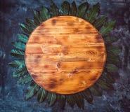 Den runda tomma träskärbrädan med lagerbladen omkring på ett mörker - gråna texturerad bakgrund Top beskådar kopiera avstånd Royaltyfri Foto