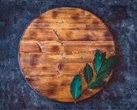 Den runda tomma träskärbrädan med lagerbladfilialen på ett mörker - gråna texturerad bakgrund Top beskådar kopiera avstånd Arkivfoto