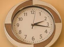 Den runda väggklockan visar tiden 2 timmar och 15 minuter på den ljusa visartavlan Royaltyfria Foton