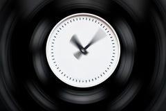Den runda vita klockan med suddiga pilar på ett mörker isolerade bakgrund Arkivfoto