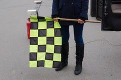 Den rutiga handhållen samlar den tävlings- startflaggan Royaltyfri Fotografi