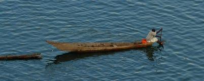 Den rwandiska mannen paddlar det långa fartyget som drar journaler Fotografering för Bildbyråer