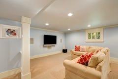 Den rymliga källarevardagsruminre i pastellblått tonar Royaltyfria Bilder