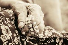 Den rynkade closeupen av den gamla kvinnan räcker att be den hållande kristna radbandet Royaltyfri Foto