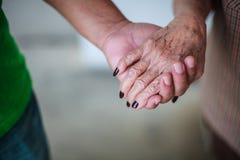 Den rynkiga äldre handen för kvinna` som s rymmer till handen för ` s för den unga mannen som går i shoppinggalleria, parkerar Fa royaltyfria bilder