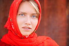 Den ryska blondinen med blåa ögon i en röd sjalett arbetar på lantgården Begreppet av kvinnlig skönhet och perfektion arkivbild