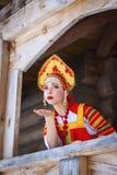 Den ryska flickan i en kokoshnik överför en luftkyss Arkivbild