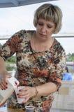Den ryska kvinnan häller fruktsaft eller vin i ett exponeringsglas Royaltyfri Foto