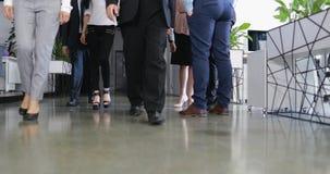 Den säkra gruppen av affärsfolk går i det moderna kontoret, lyckade det rörande coworkerslaget framåtriktat arkivfilmer