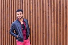 Den säkra gulliga unga muslimska mannen poserar och ser kameran, leende fotografering för bildbyråer