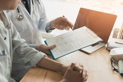 Den säkra kvinnliga doktorn granskar tålmodig medicinsk information och royaltyfri bild