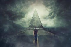 Den säkra luffaregrabben gå en overklig väg och grundar en magisk trappa som upp till går en dörr i himlen royaltyfri foto