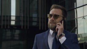 Den säkra manliga chefen talar på telefonanseende på modern byggnadsbakgrund lager videofilmer