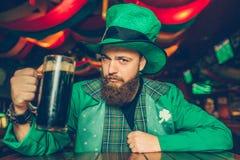 Den säkra och allvarliga unga mannen i gröna Sts Patrick dräkt sitter på tabellen i bar och poserar på kamera Han rymmer rånar av royaltyfri bild