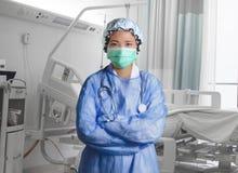 Den säkra och lyckade asiatiska koreanska medicindoktorskvinnan i sjukhus skurar och maskeringen som in poserar på tålmodig säng  royaltyfri foto