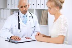 Den säkra skalliga doktorsmannen konsulterar hans kvinnliga patient royaltyfria bilder
