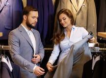 Den säkra stiliga mannen med skägget som väljer ett omslag i en dräkt, shoppar Arkivfoton