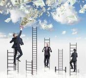 Den säkra stiliga mannen på stegen tilldrar dollaranmärkningar genom att använda en magnet Himmel med moln på bakgrunden royaltyfri foto