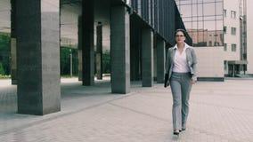Den säkra unga affärskvinnan överförs till kontorsbyggnaddokumenten lager videofilmer