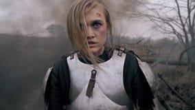 Den sårade blondinen med en sår på hennes huvud står i röken arkivfilmer