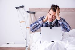 Den sårade mannen som direktanslutet hemma pratar via webcam i säng Royaltyfri Fotografi