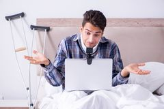 Den sårade mannen som direktanslutet hemma pratar via webcam i säng Arkivbilder