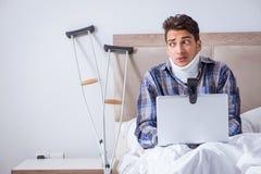 Den sårade mannen som direktanslutet hemma pratar via webcam i säng Royaltyfri Bild